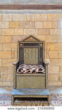 Wooden chair with arabesque seamless pattern based on hexagram (star of David) on stone bricks wall
