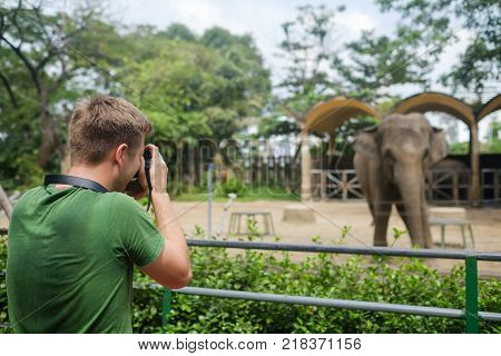 Ho Chi Minh city, Vietnam - December 05, 2017: caucasian tourist man photographing elephant with his camera in Ho shi min zoo, Vietnam