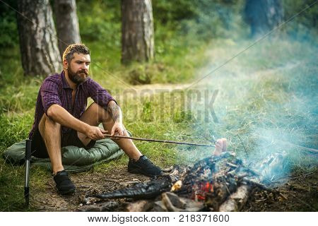 Man hiker roast sausages on stick on bonfire in forest. Summer camping hiking vacation. Picnic barbecue cooking food concept.