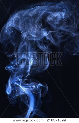 Abstract background with smoke. Blue smoke on black background. Smoking cloud backdrop. Spirit and ghost miracle. Blue ink in freeze motion powder splatted explosion.