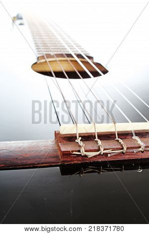 Guitar artsy POV background. Music illustration. Black and white guitar closeup. Music classic instrument. Black guitar with white reflection. Photo.