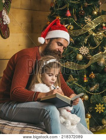 Christmas happy child and father read book. Santa claus kid and bearded man at Christmas tree. Xmas party celebration fathers day. Winter holiday and vacation. New year small girl and man fairytale.