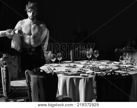 Female hand with wine glass and handsome man or sexy muscular macho athlete in unbutton shirt at table with leftovers food on dirty plates after banquet in restaurant on dark background