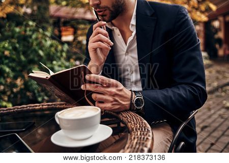 Busy day. Close up of young man in smart casual wear checking notes in personal organizer while sitting in restaurant outdoors
