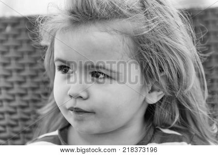 childhood and happiness. happy cute baby boy small little child with adorable face brown eyes long blond hair smiling on sunny summer day outdoors on brown wicker background