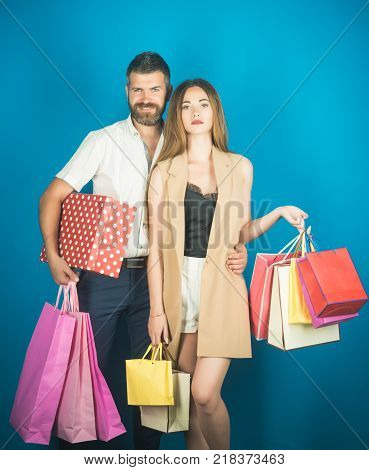 Couple in love hold shopping bag near blue wall. Girl and bearded man hold present pack cyber Monday. Shopping and sale. Fashion shopaholic couple. Black Friday happy holiday relations.