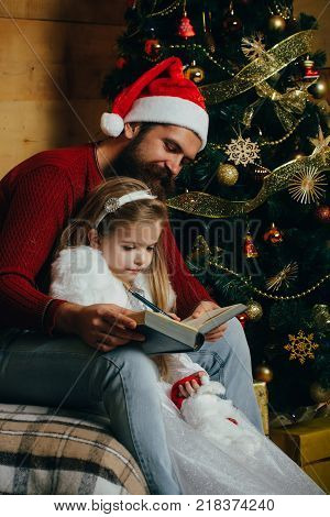 Santa claus kid and bearded man at Christmas tree. Christmas happy child and father read book. Winter holiday and vacation. Xmas party celebration fathers day. New year small girl and man fairytale.