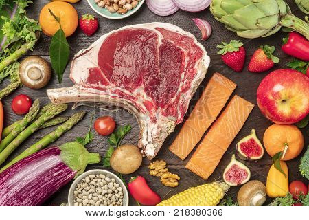 An overhead photo of various foods. Fresh vegetables, fruits, legumes, fish, and meat. Balanced diet ingredients, shot from above on a dark rustic texture. Organic food or groceries shop banner