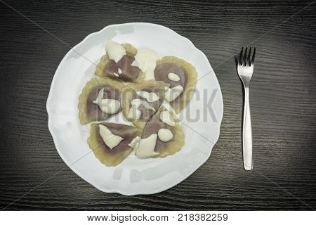 Top view of a plate with dumplings filled with cottage quark and blueberry.