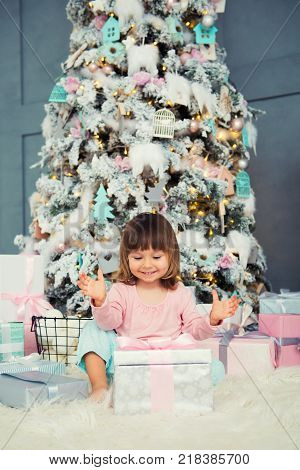 Positive cheerful baby girl sitting with Christmas gift near Christmas tree. Happy New Year.