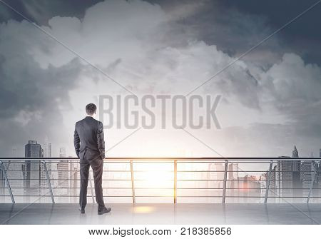 Businessman Looking At A Gray City From A Balcony
