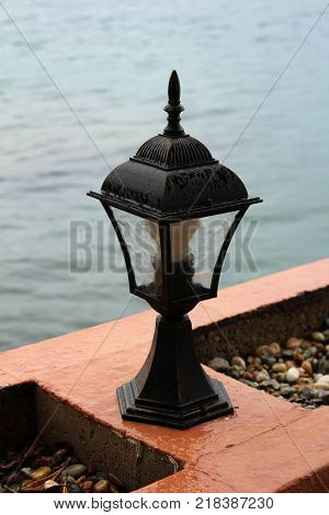 Black baroque style street lamp covered with raindrops on rainy day mounted on stone wall next to sea