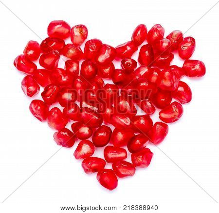 heartshaped scattered pomegranate grain isolated on white background