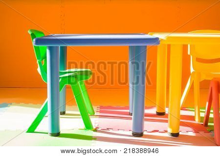 Colorful plastic chair and desk for children playing and learning in kids room in vintage style. (Selective focus)