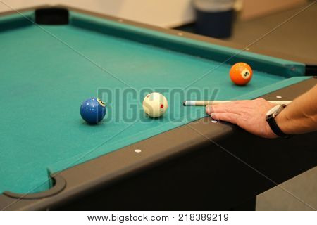 Billiard balls on green table and hand with billiard cue