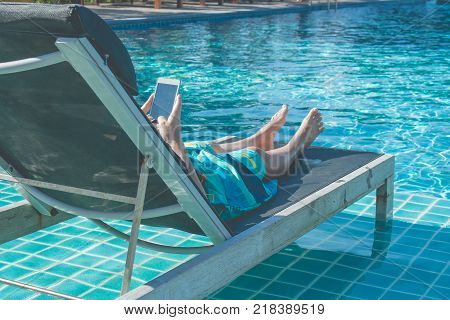 Woman lying in daybed and playing her smartphone beside swimming pool. (Selective focus)