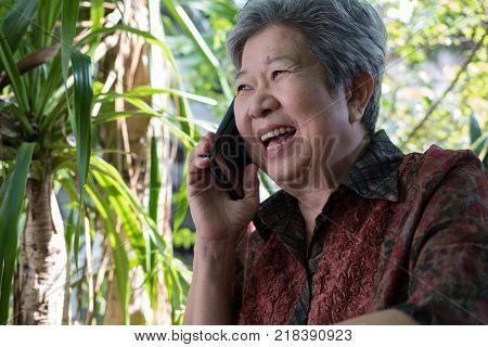 elder woman talk on mobile phone in garden. elderly female speaking on smartphone in park. asian senior have phone conversation