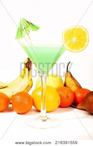 Tropical fruit cocktail concept. Cocktail with umbrella colorful illustration on isolated white studio background. Sexy delicious fashion drinks. Alcohol cocktails. Blue green cocktail with pear banana orange blue curacao. Studio photo.