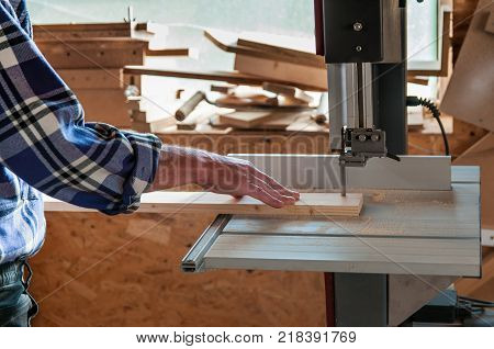 Cutting pine board at the band saw in a small workshop