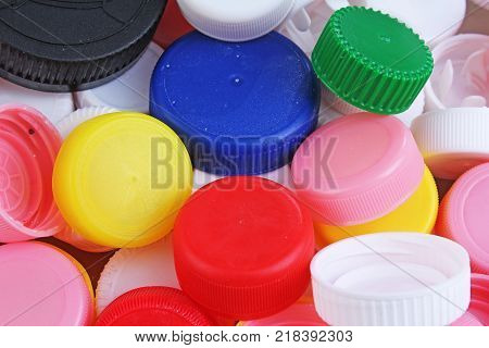 Collect plastic bottle caps. Close-up shot of stack of recyclable plastic bottle caps on white background. Bottle cap texture pattern as background. Colorful plastic cap.