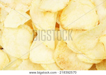 Chips pattern. Yellow salted potato chips as background. Chips texture studio photo. Food.