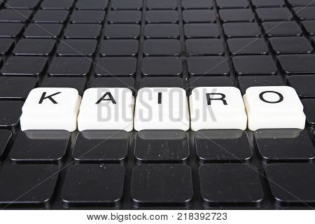poster of Kairo title text word crossword. Alphabet letter blocks game texture background. White alphabetical letters on black background. White educational toy block with words on board table. Words.