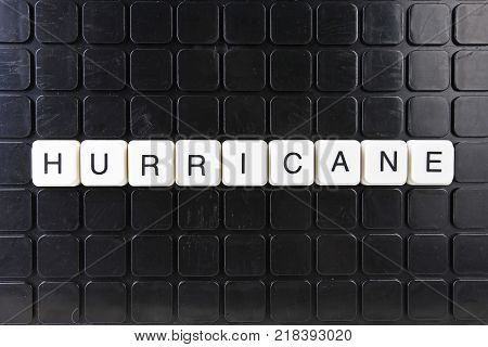 poster of Hurricane title text word crossword. Alphabet letter blocks game texture background. White alphabetical letters on black background. White educational toy block with words on board table. Words.