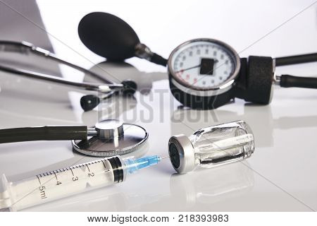 Medical equipment. Cardiologist sphygmomanometer or blood pressure meter, ampoule with medicine drug, syringe and medical stethoscope isolated on white background close-up. Healthcare medicine concept