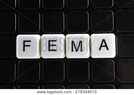 poster of Fema title text word crossword. Alphabet letter blocks game texture background. White alphabetical letters on black background. White educational toy block with words on board table. Words.