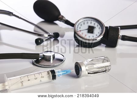 Cardiology medical equipment. Cardiologist sphygmomanometer or blood pressure meter, ampoule with medicine drug, syringe and medical stethoscope isolated on white background close-up.