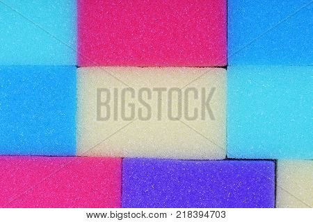 Cleaning kitchen sponge texture as background. Colorful yellow pink green purple blue multicolor sponges. Close up macro about sponges. Sponge pattern textures concept background or wallpaper Sponges.