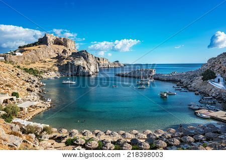 Beautiful beach in St. Paul´s bay Lindos acropolis in background (Rhodes Greece)