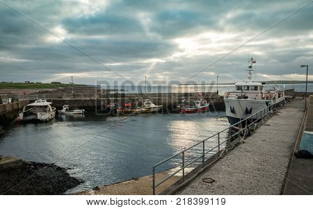 JOHN O'GROATS SCOTLAND - 28 JUNE 2017: A dusk view of the small harbour at John O'Groats Scotland with the Orkney passenger ferry in port.