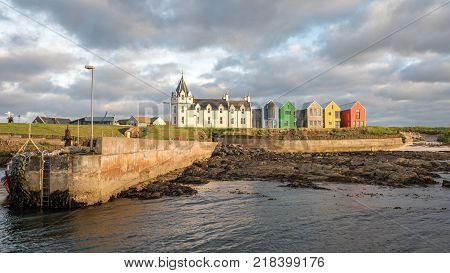 JOHN O'GROATS SCOTLAND - 28 JUNE 2017: A dusk view from the sea of the Natural Retreats Hotel that dominates the John O'Groats coastline on the northern point of the UK mainland.