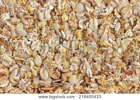 mixture of 7 types of cereal flakes (wheat oats rye barley buckwheat rice millet). The concept of proper nutrition and healthy lifestyle. Top view close-up as background or texture