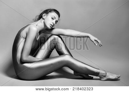 young sexy fit woman or girl with slim body and pretty face in fitness sporty violet jumpsuit or overalls posing in studio on grey background