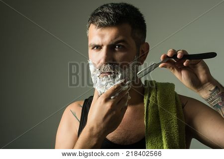 Serious hipster in barbershop new technology. Man cut beard and mustache with razor and shaving brush. Haircut of bearded man archaism. Barber and hairdresser. Fashion and beauty innovation.