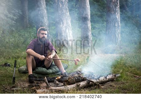 Man traveler roast sausages on stick on campfire in forest. Summer camping hiking vacation. Picnic barbecue cooking food concept.