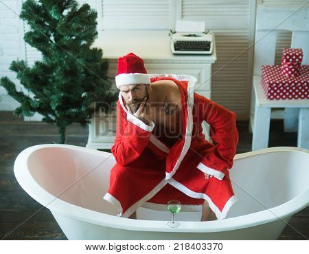 Hipster santa at Christmas tree drink wine loneliness. Christmas man with beard waiting. Home alone bad santa in bath. Winter holiday and xmas party. Expectation love and betrayal.