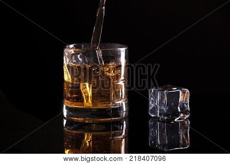 Emotive image of pouring liquor. A studio image of a glass filled with ice and liquor.