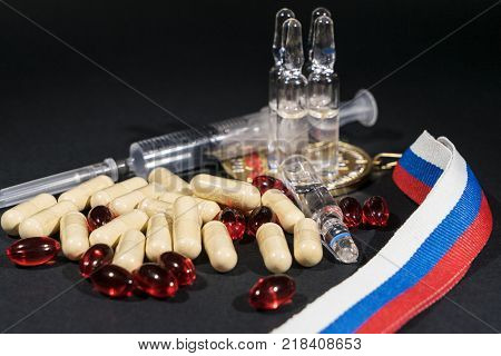 tablets pills and syringe of doping drugs or medicine with russian tape flag on the dark background poster