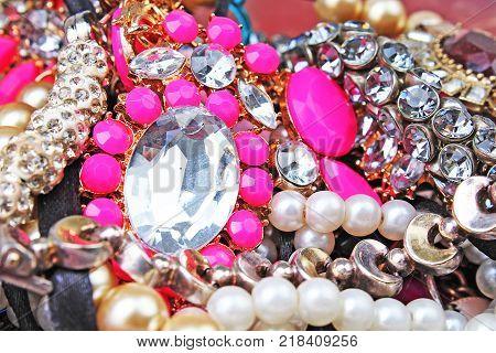 Fashion jewelrys. Fashion jewels as background. Jewelery texture. A lot of Jewells in texture. Jewellery background. Beautiful jewels pattern.Necklace pearls. Pink rhinestones.