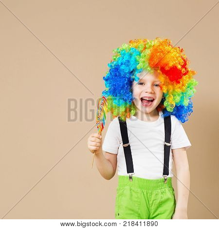 Happy Clown Boy In Large Colorful Wig. Let's Party! Funny Kid Clown. 1 April Fool's Day Concept. Por
