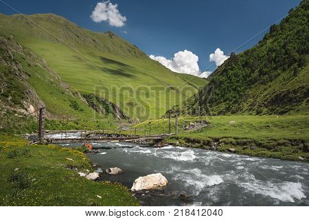 Landscape of a mountain valley with view at mountain river and mountain range. Blue sky with clouds over mountains. Bridge over a mountain river.