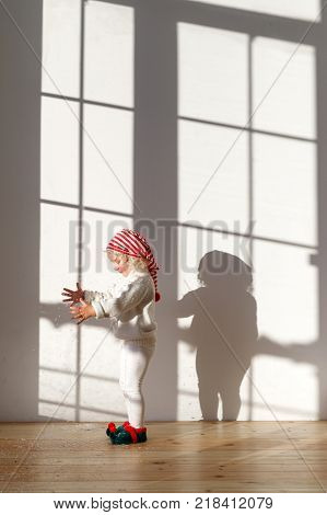 Small adorable blonde pretty female girl stands in spacious room, wears white costume, red hat and elf s shoes plays with something, being along, anticipates coming holidays. Childhood concept