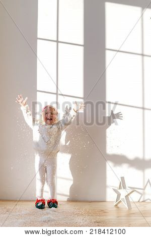 Vertical shot of overjoyed small girl dressed in white sweater and leggins, wears elf s shoes, plays with artificial snow indoor, stands against big spacious window. Children and happiness concept.
