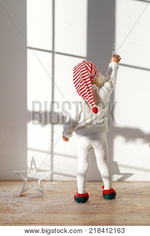Back view of adorable small kid elf wears white costume, santa s hat and elf s shoes, plays with artificial snow, stands on wooden floor in spacious room, likes playig. Children, celebration concept.
