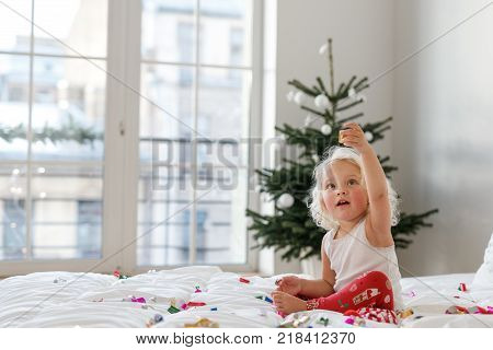 Children, Christmas and New Year concept. Adorable blonde female child wears pyjamas, plays with colourful confetti on comfortable bed, enjoys winter and holidays, decorated fir tree in background