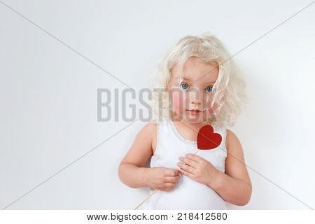 Beautiful serious blue eyed small child with rouge cheeks, dressed casualy, has blonde curly hair, holds stick in form of heart, isolated over white studio background. Children, facial expressions