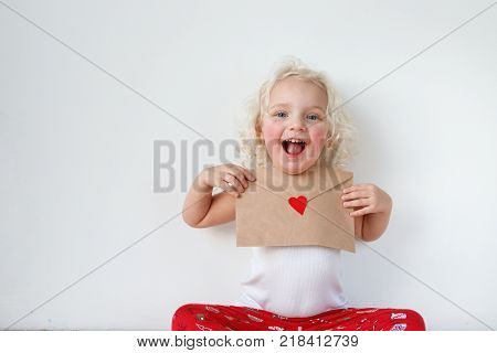Portrait of adorable small kid has cheerful expression, holds letter to Santa Claus, hopes her dreams come true, isolated over white background. Cheerful little child with letter. Beauty and childhood.